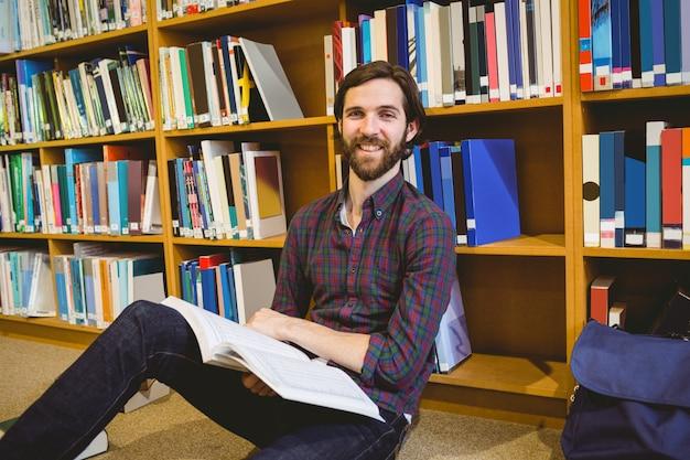Studentenlesebuch in der bibliothek auf fußboden