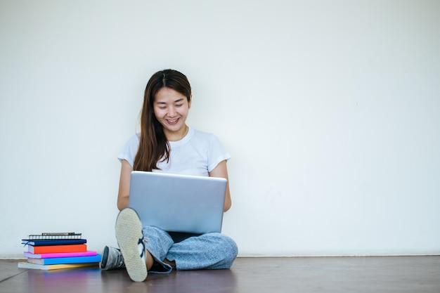 Studentenmädchen, das bericht mit laptop macht und in der schule sitzt.
