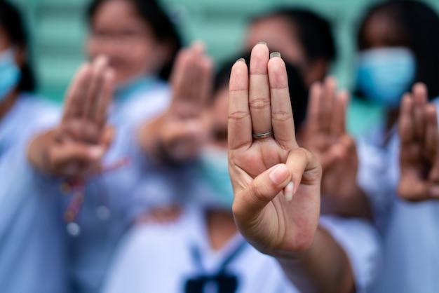 Studentenmädchen, das drei fingergruß in der schule zeigt
