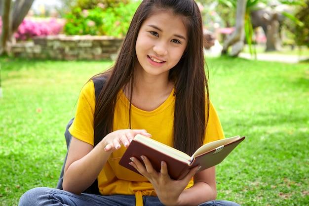 Studentenmädchen, das ein buch im park liest