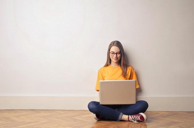 Studentenmädchen, das einen laptop verwendet