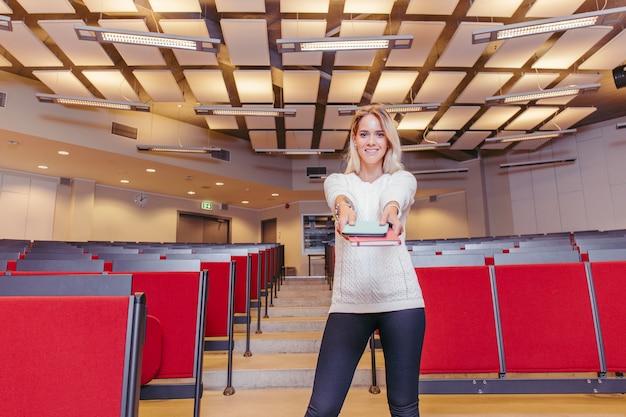 Studentenmädchen mit büchern im hochschulamphitheater