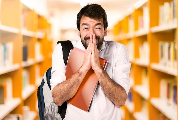 Studentenmann, der auf defocused bibliothek plädiert