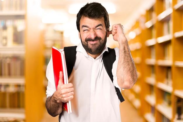 Studentenmann, der seine ohren auf defocused bibliothek bedeckt