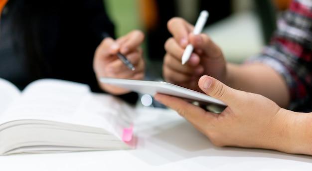 Studentenmannhand, die tablette hält und stift für das bitten verwendet