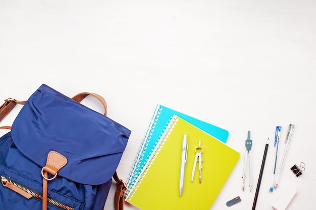 Studentenrucksack und verschiedene schulsachen. studing, bildung und zurück zum schulkonzept