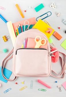Studentenrucksack und verschiedene schulsachen. studium, bildung und zurück zum schulkonzept