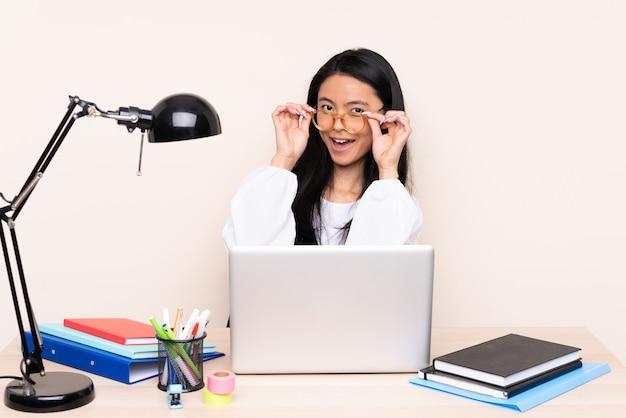 Studentin an einem arbeitsplatz mit einem laptop auf beige mit brille isoliert und überrascht