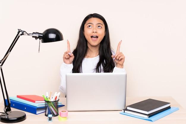 Studentin an einem arbeitsplatz mit einem laptop, der auf beige isoliert und nach oben zeigt