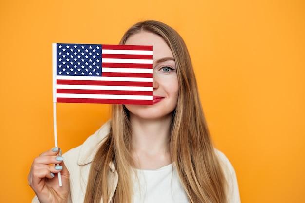 Studentin bedeckt halbes gesicht mit kleiner amerikanischer flagge