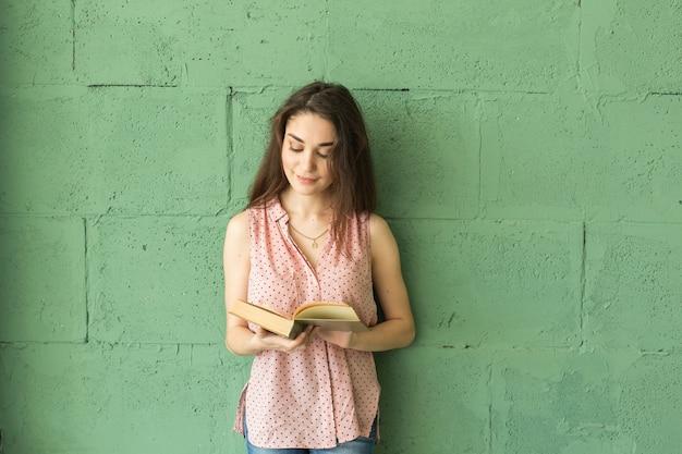Studentin beim lesen des buches über der grünen wand