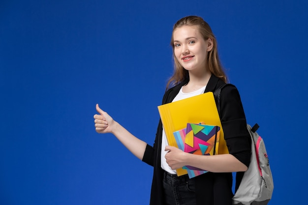 Studentin der vorderansicht im weißen hemd und in der schwarzen jacke, die rucksack hält, der dateien mit heften auf den blauen wanduniversitätsuniversitätsstunden hält