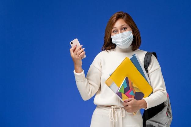 Studentin der vorderansicht im weißen trikot, das maske und rucksack hält telefon mit kopfhörern auf blauen wanduniversitäts-universitätsbuchstunden hält