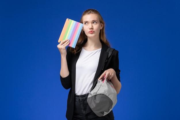 Studentin der vorderansicht in der schwarzen jacke, die grauen rucksack und heft auf der blauen wandschule collegeuniversitätsunterrichtszeit hält
