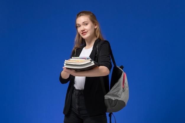 Studentin der vorderansicht in der schwarzen jacke, die rucksack hält bücher hält, die auf der blauen wandzeichnung kunstschulhochschule lächeln
