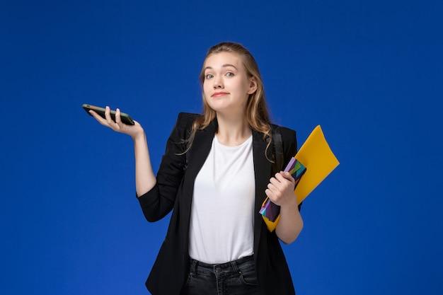 Studentin der vorderansicht in der schwarzen jacke, die rucksack hält datei und heft mit telefon auf blauen wand college-universitätsunterrichtsbüchern trägt