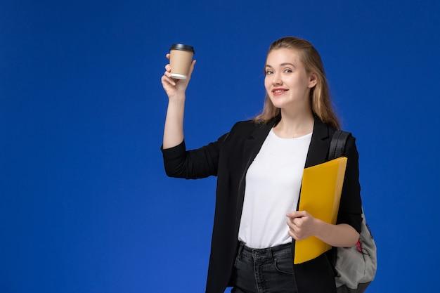 Studentin der vorderansicht in der schwarzen jacke, die rucksack hält, der gelbe datei und kaffee auf universitätsunterricht der blauen wandschule hält