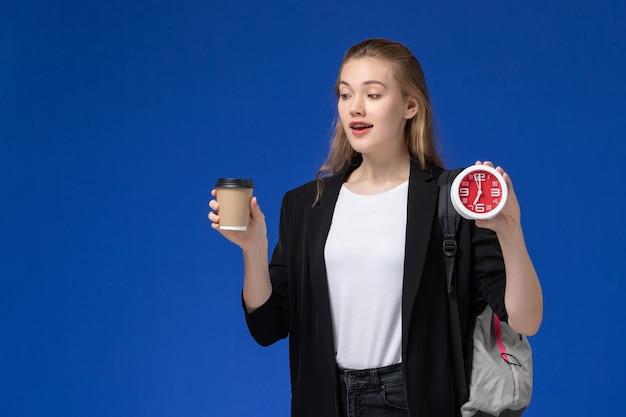 Studentin der vorderansicht in der schwarzen jacke, die rucksack hält, der uhren und kaffee auf der blauen wandschule college-universitätsstunde hält