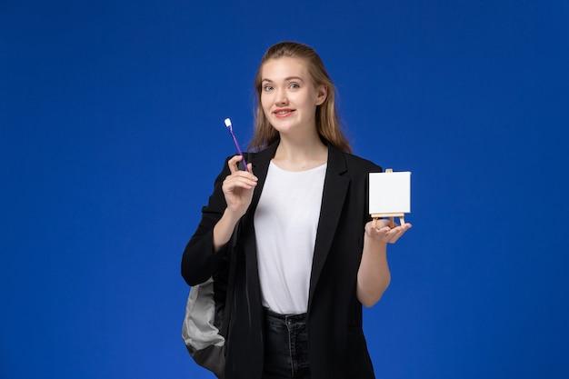 Studentin der vorderansicht in der schwarzen jacke, die rucksack hält staffelei auf der blauen wandzeichnung kunstschule college