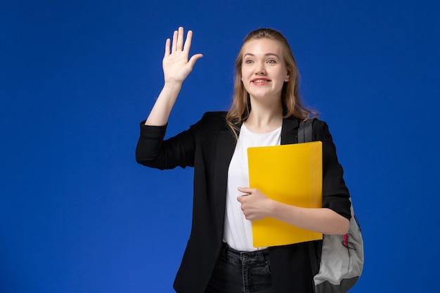 Studentin der vorderansicht in der schwarzen jacke, die rucksack trägt und gelbe datei hält, die auf den universitätsstunden der blauen wandschule college winkt