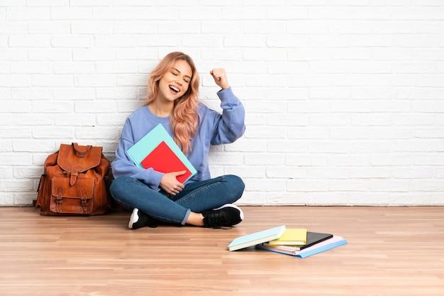 Studentin des teenagers mit rosa haaren, die auf dem boden drinnen sitzen und einen sieg feiern