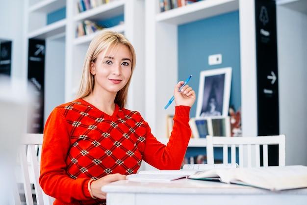 Studentin, die am schreibtisch sitzt