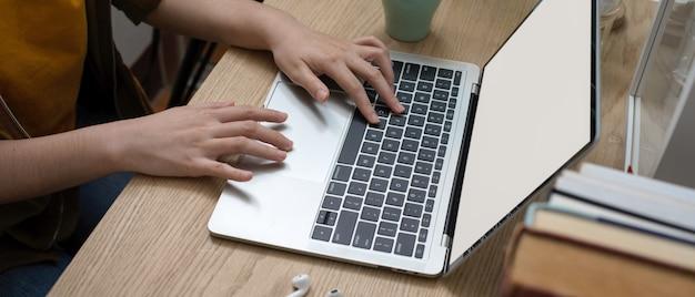 Studentin, die an ihrer aufgabe mit laptop des leeren bildschirms auf hölzernem arbeitstisch arbeitet