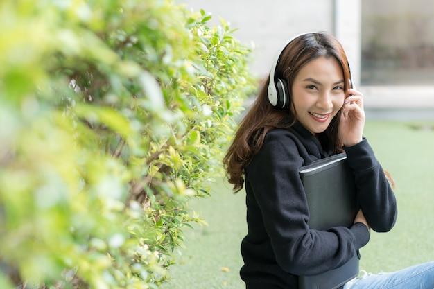 Studentin, die auf rasenbank am campus sitzt