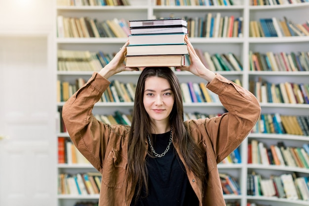 Studentin, die bücher auf ihrem kopf balanciert, in der universitätsbibliothek steht und kamera betrachtet. schönes mädchen hält einen stapel bücher auf dem kopf und lächelt
