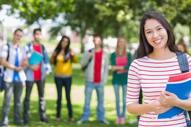 Studentin, die bücher mit unscharfen studenten im park hält