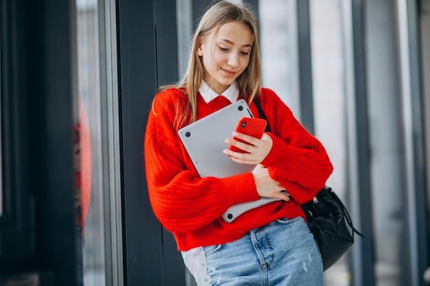Studentin, die computer hält und am telefon durch das fenster spricht