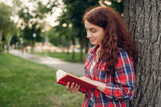 Studentin, die das buch im sommerpark studiert. ingwer teenager freizeit im freien, hübsches mädchen entspannen sich draußen
