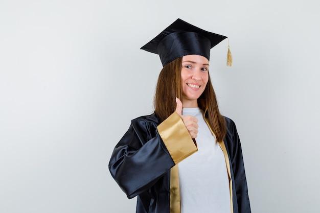 Studentin, die daumen oben im abschlusskleid zeigt und fröhlich schaut. vorderansicht.