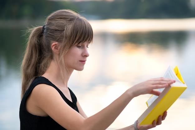 Studentin, die draußen im sommerpark sitzt und lehrbuch liest. bildungs- und studienkonzept.