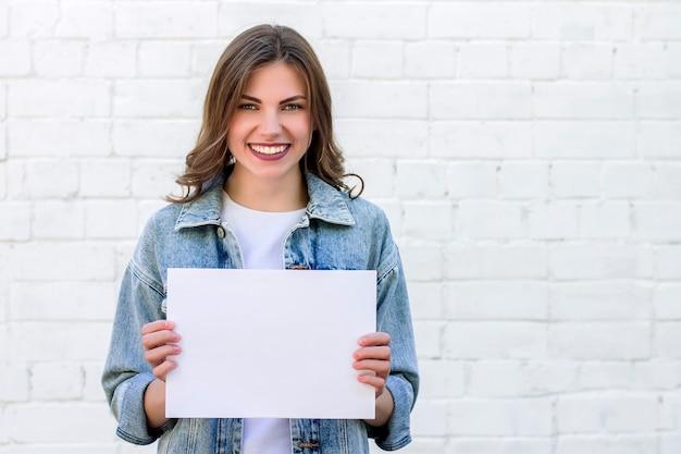 Studentin, die ein weißes blatt papier auf einem hintergrund einer weißen backsteinmauer lächelt und hält