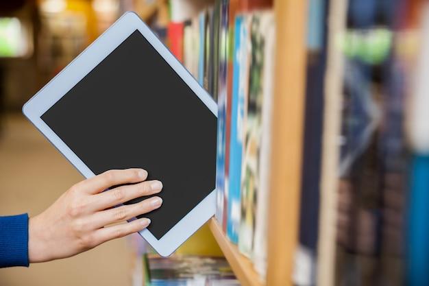 Studentin, die eine tablette in einem bücherregal in der bibliothek an der universität aufräumt