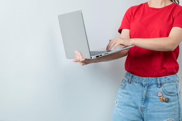 Studentin, die einen grauen laptop hält