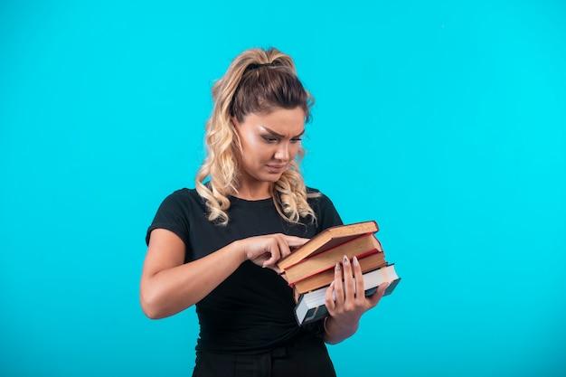 Studentin, die einen schweren bestand an büchern hält und liest.