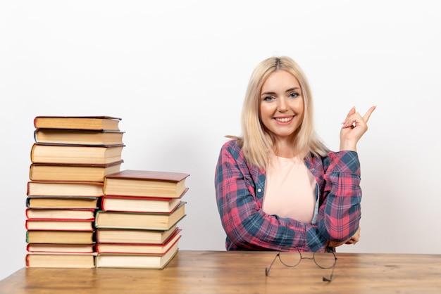 Studentin, die gerade mit büchern auf weiß sitzt