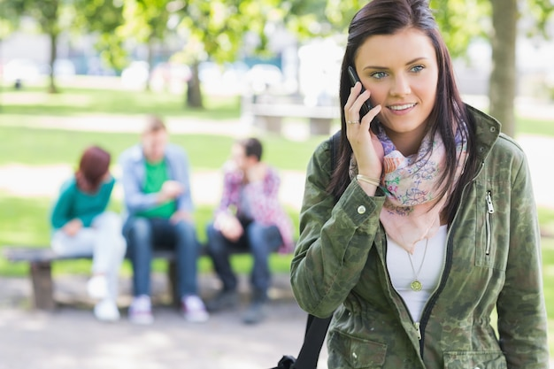Studentin, die handy mit studenten im park verwendet