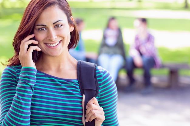 Studentin, die handy mit unscharfen studenten im park verwendet