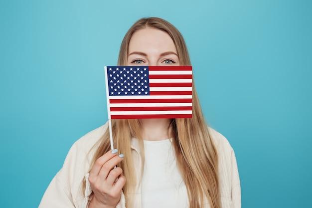 Studentin, die ihr gesicht mit einer kleinen amerikanischen flagge bedeckt