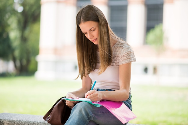 Studentin, die in einem park vor der schule studiert