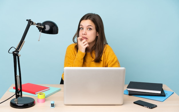 Studentin, die in ihrem haus studiert, isoliert auf blauer wand nervös und verängstigt