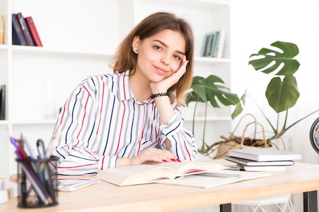 Studentin, die mit buch und dem lächeln sitzt