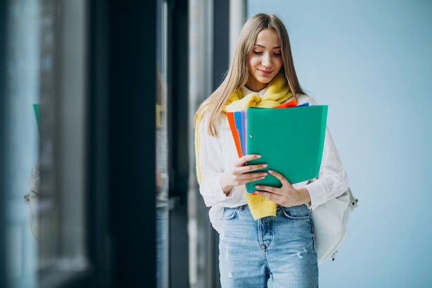 Studentin, die mit bunten ordnern steht