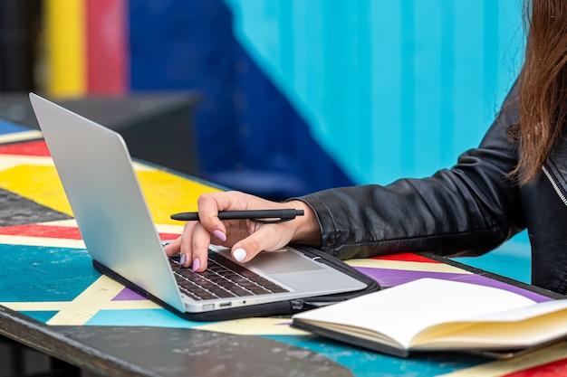 Studentin, die mit laptop am straßencafé sitzt und arbeitet