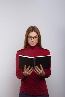 Studentin, die notizbuch hält und schaut
