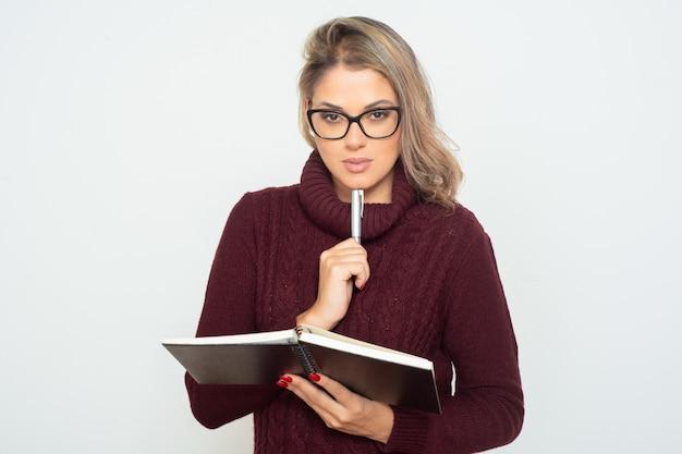 Studentin, die notizbuch und stift hält