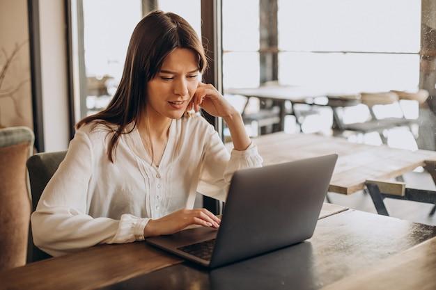 Studentin, die online in einem café studiert